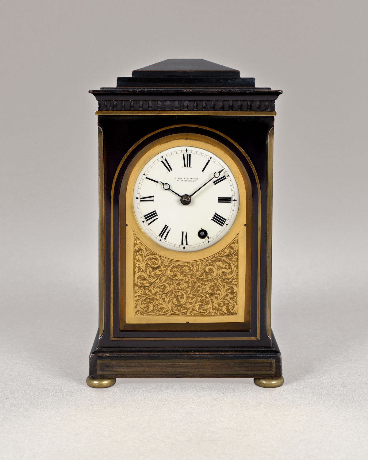 FINER & NOWLAND, HIGH HOLBORN. A FINE AND SMALL REGENCY PERIOD TIMEPIECE IN AN EBONISED CHAMFER TOP CASE.